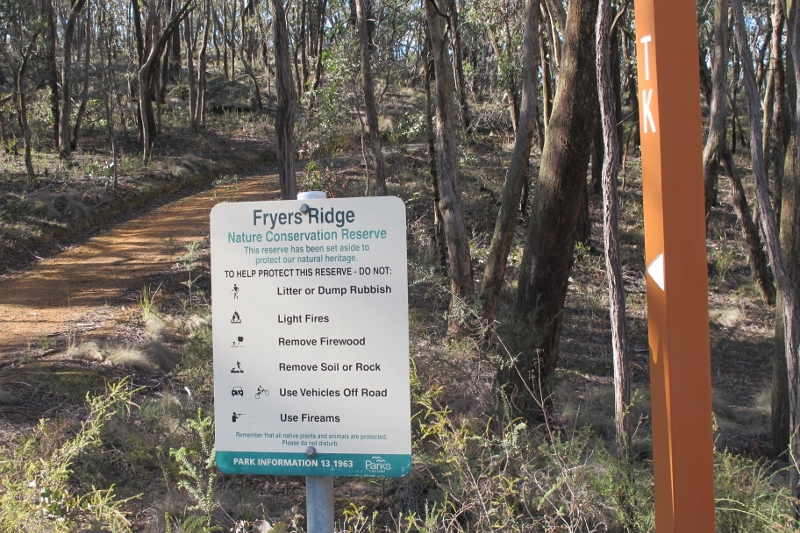 Sign on Fryers Ridge: it doesn't sit well next to the gouging of the nearby Ridge Road. FOBIF has argued that road works should be planned with careful concentration given to adjacent bushland.